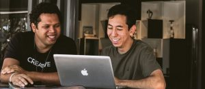 Two men looking at computer smiling