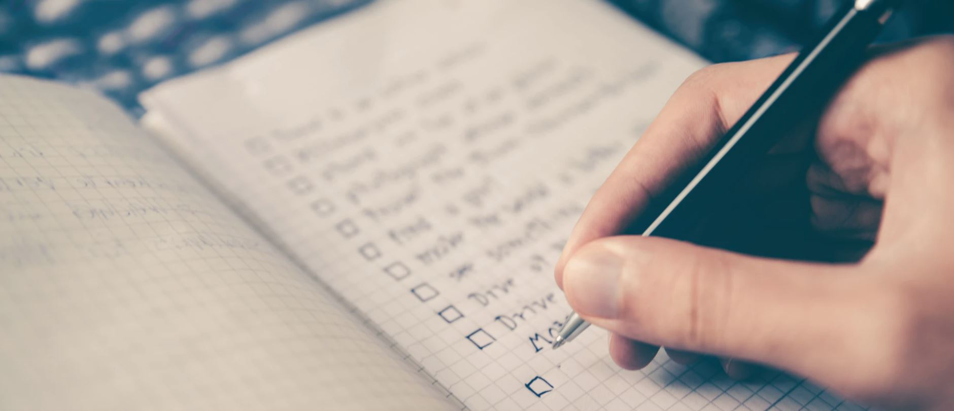 Person making list of goals in notebook