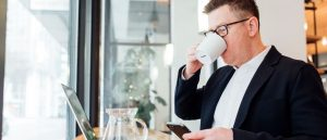Man in suit drinking coffee with laptop