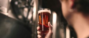 Man holding beer in pint glass