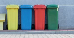 four assorted color garbage removal cans