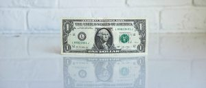 one dollar bill on white surface