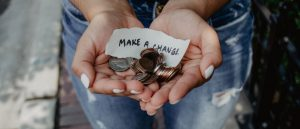 Woman holdiy charitable donation of change